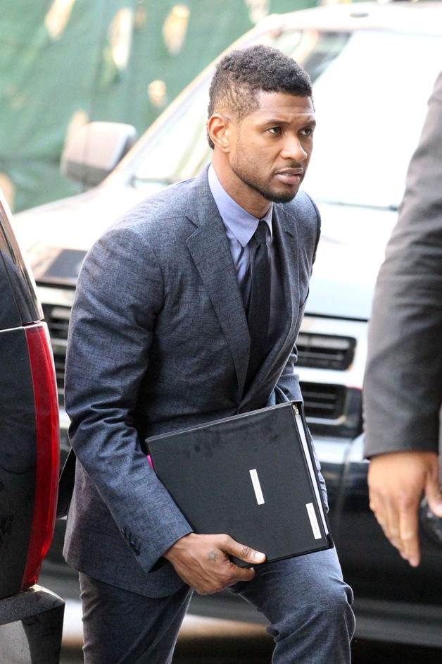 Usher carries a script for the 2014 movie 'Hands of Stone' as he heads into his Downtown hotel in New York City