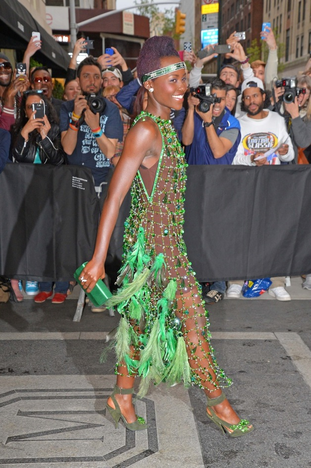 Lupita Nyong'o seen posing smiling showing off her sexy glamorous see through outfit with green feathers at the Met Gala and theafter party in NYC