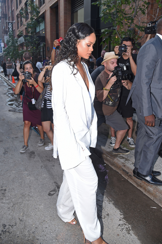 Rihanna rocks a plunging white suit and brown heels at Edun Fashion Show in New York City